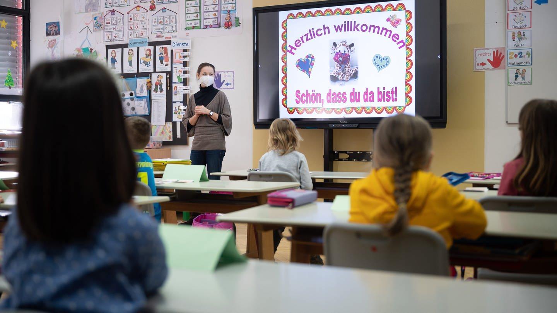Eine Lehrerin mit FFP2-Maske unterrichtet in einer ersten Klasse an einer Grundschule mit Wechselunterricht. (Foto: dpa Bildfunk, picture alliance/dpa | Sebastian Gollnow (Symbolbild))