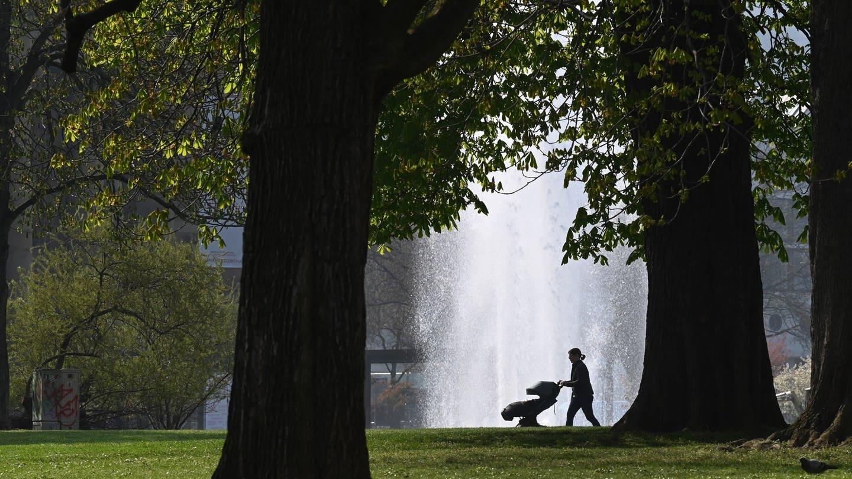 Eine Frau geht im Stuttgarter Schlossgarten spazieren und schiebt einen Kinderwagen an einer Wasserfontäne vorbei. (Foto: dpa Bildfunk, picture alliance/dpa | Bernd Weissbrod)