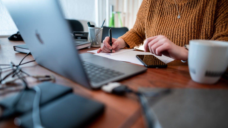 Eine Frau sitzt mit einem Laptop an einem Tisch im Homeoffice. (Foto: dpa Bildfunk, picture alliance/dpa   Fabian Strauch)
