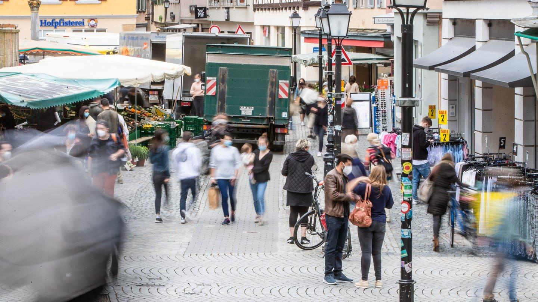 Menschen gehen durch die Fußgängerzone. Geschäfte, die wegen der