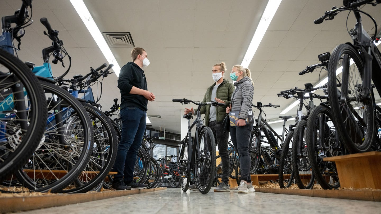 Ein Mann und eine Frau stehen in einem Fahrradgeschäft einem Verkäufer gegenüber