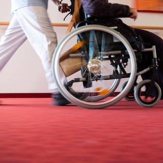 Ein Pfleger eines Pflegeheims schiebt eine Bewohnerin mit einem Rollstuhl. (Foto: dpa Bildfunk, picture alliance/dpa | Tom Weller)