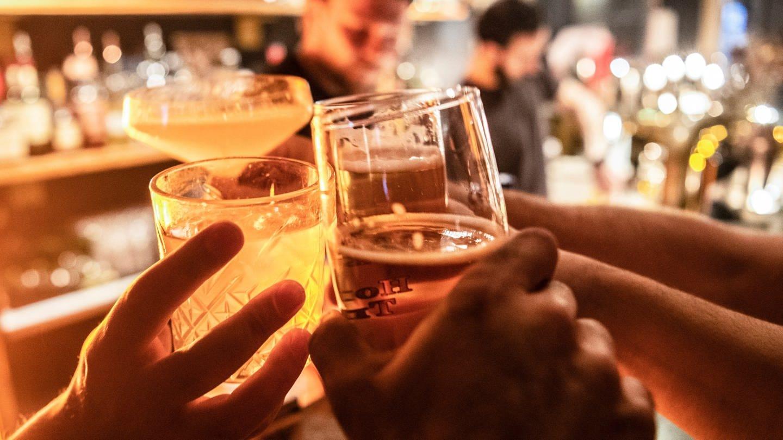 Gäste prosten sich in einer Bar zu.