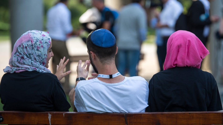Zwei junge Muslimas mit Kopftuch und ein junger jüdischer Mann mit Kippa unterhalten sich miteinander.