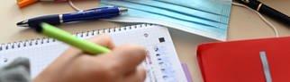 Eine Mund-Nase-Schutzmaske liegt zwischen Schreibutensilien auf einem Tisch, während ein Schüler einen Stift über einem Schreibblock hält. (Foto: dpa Bildfunk, picture alliance/dpa | Uli Deck)