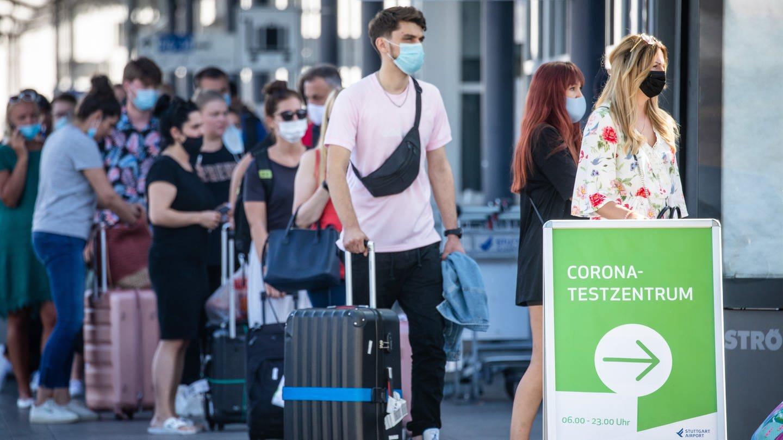 Reiserückkehrer stehen mit Mundschutz vor dem Corona-Testzentrum am Flughafen Stuttgart.