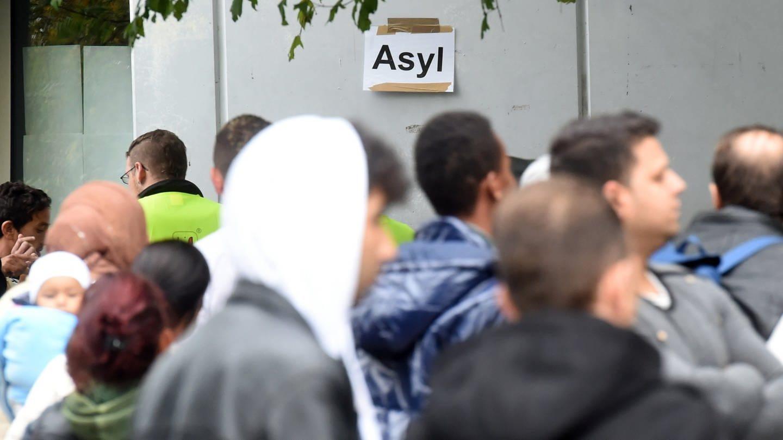 In der Landeserstaufnahmestelle (LEA) für Flüchtlinge in Karlsruhe (Baden-Württemberg) warten am 08.10.2014 Flüchtlinge auf ihre Registrierung. Im Hintergrund ist ein Papier an der Wand angebracht, auf dem das Wort