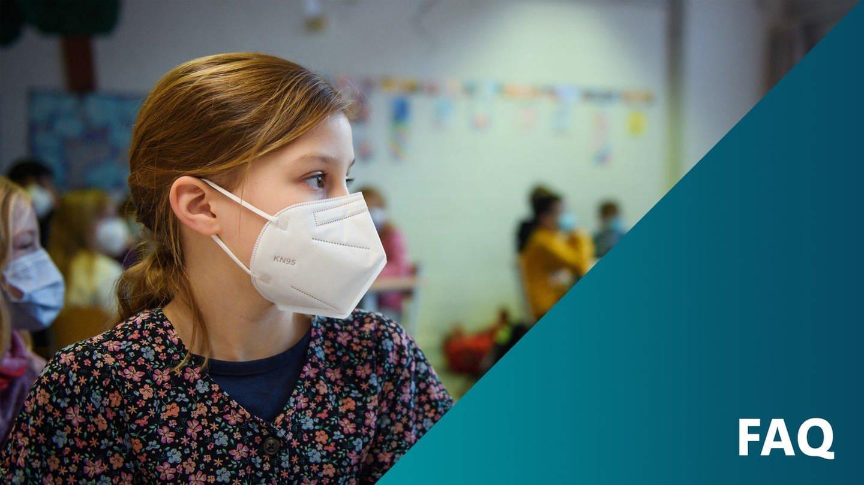 Kind sitzt mit einer Corona-Maske in einem Klassenzimmer in einer Schule