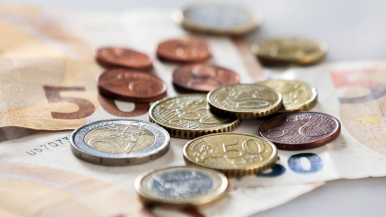 Geldscheine- und Münzen auf einem Tisch.