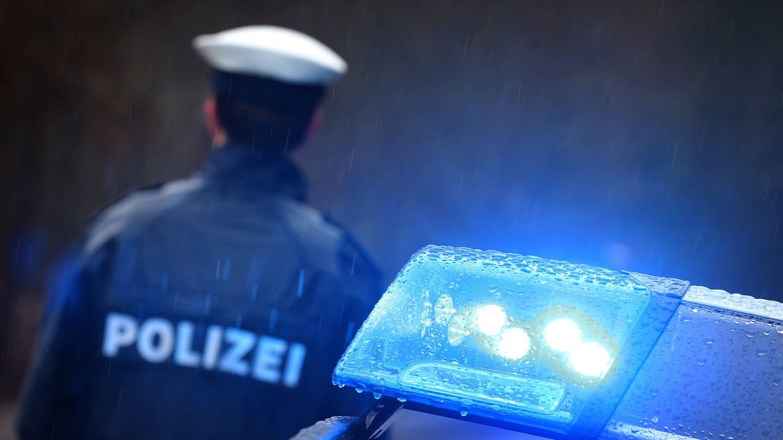Ein Polizist steht hinter dem Blaulicht eines Streifenwagens