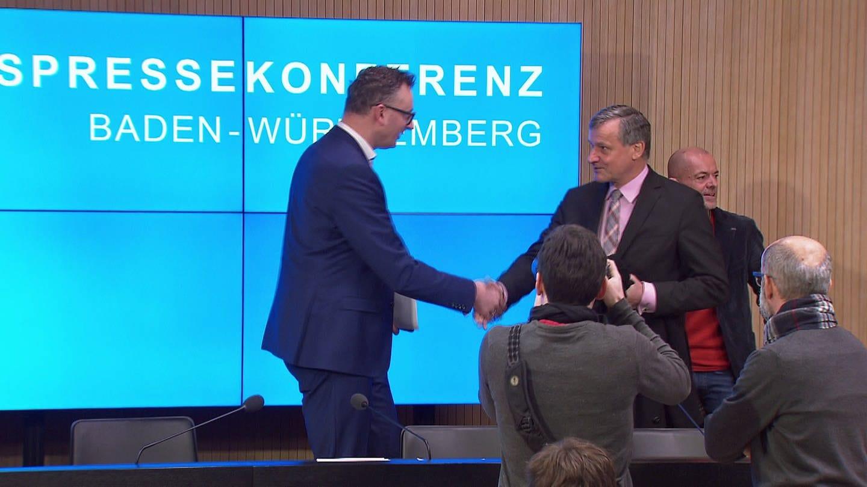 Die Fraktionsvorsitzenden im Landtag von Baden-Württemberg, Andreas Schwarz (Grüne) und Hans-Ulrich Rülke (FDP), schütteln sich auf der Landespressekonferenz in Stuttgart die Hand. (Foto: SWR)