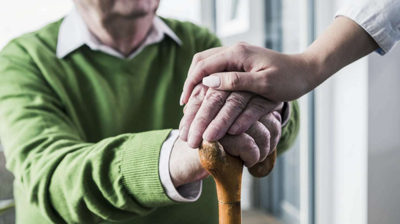 Eine Frau legt ihre Hand auf die Hände eines älteren Mannes (Foto: SWR)
