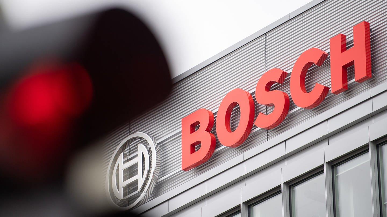 Eine rote Ampel leuchtet vor dem Logo von Bosch (Foto: picture alliance/Sebastian Gollnow/dpa)