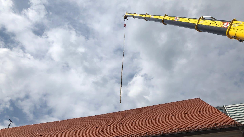 Der Narrenbaum wird per Autokran übers Dachfenster im Stadtmuseum Stockach aufgestellt