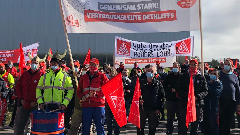 Männer stehen mit IG Metall Fahnen und roten Pfeifen auf einem Platz.