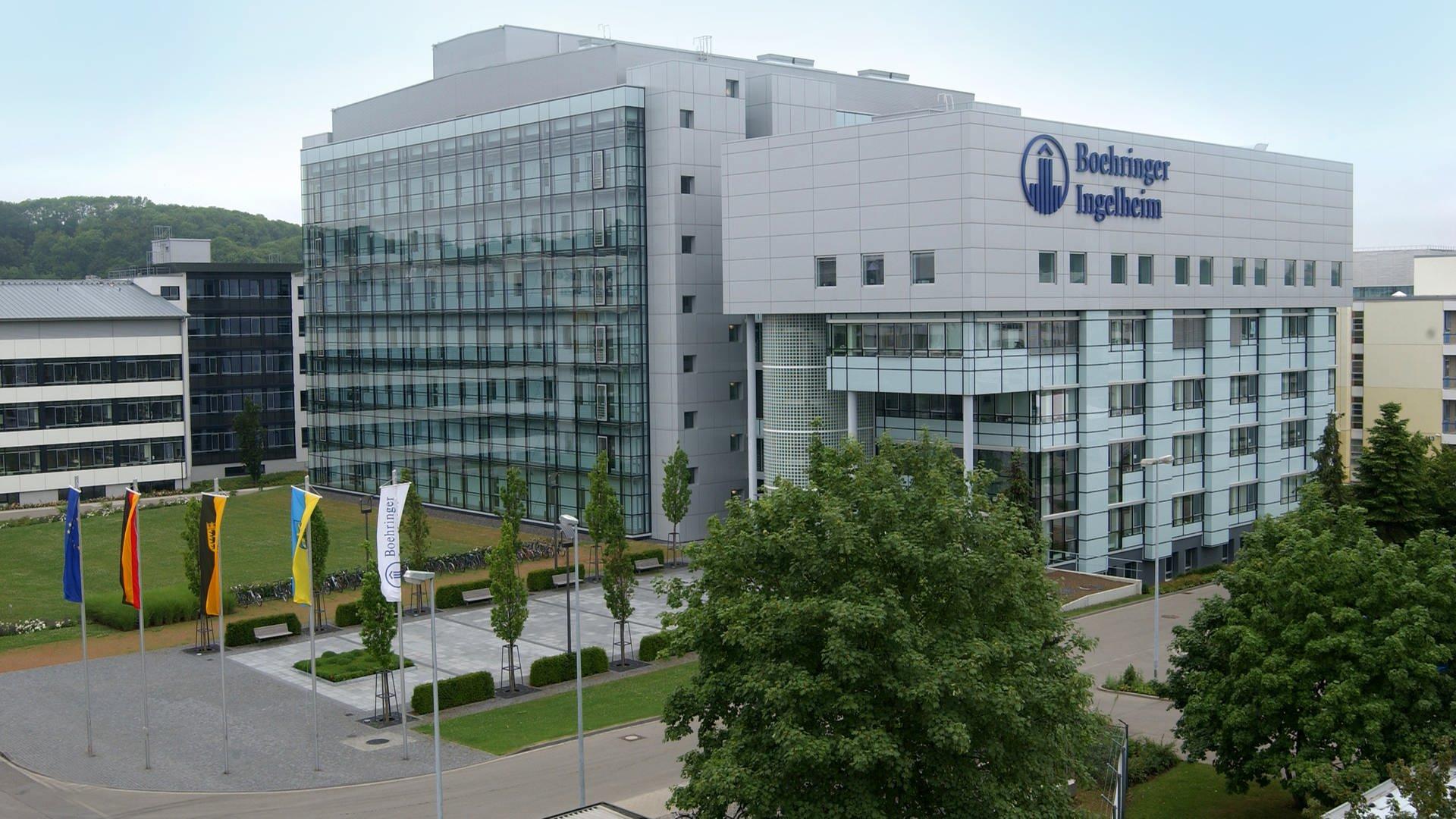 Firmengebäude des Pharmakonzerns Boehringer Ingelheim für die Biopharmazie in Biberach aus Glas und grauem Beton. Auf der Vorderseite des Gebäudes steht in großen, blauen Buchstaben der Firmenname.