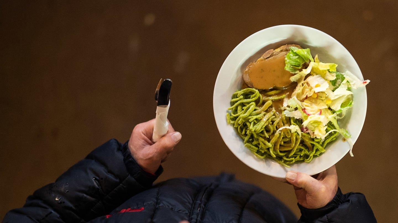 Ein Mann geht während des ersten Tags der Vesperkirche mit einem Teller Essen durch die Kriche. (Foto: dpa Bildfunk, picture alliance/Sebastian Gollnow/dpa)