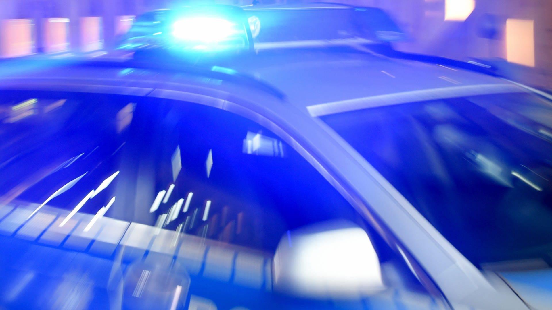 Ein Polizeiauto fährt bei Nacht mit Blaulicht