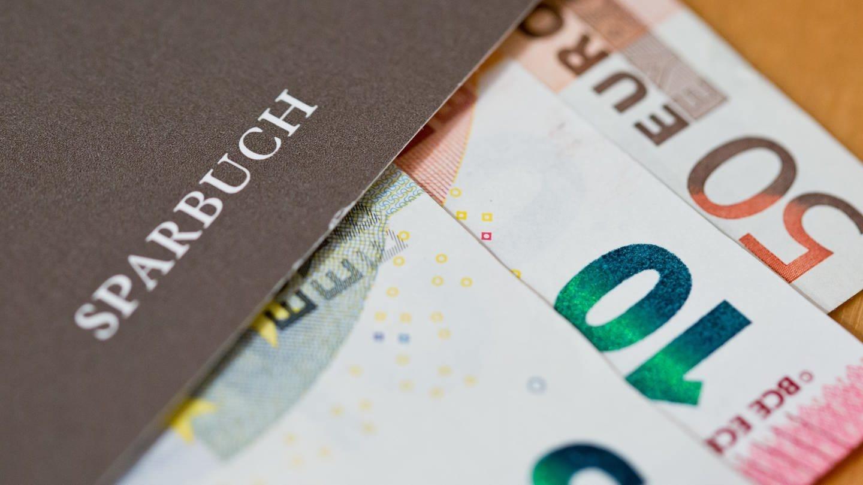 Geldscheine liegen in einem Sparbuch (Foto: picture-alliance / Reportdienste, Picture Alliance)