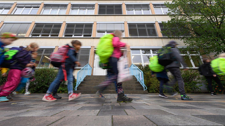 Schüler laufen vor einer Schule