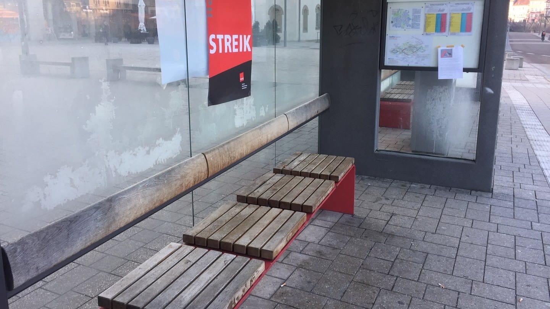 Eine leere Bushaltestelle in Schwäbsich Hall mit einem roten Plakat, auf dem