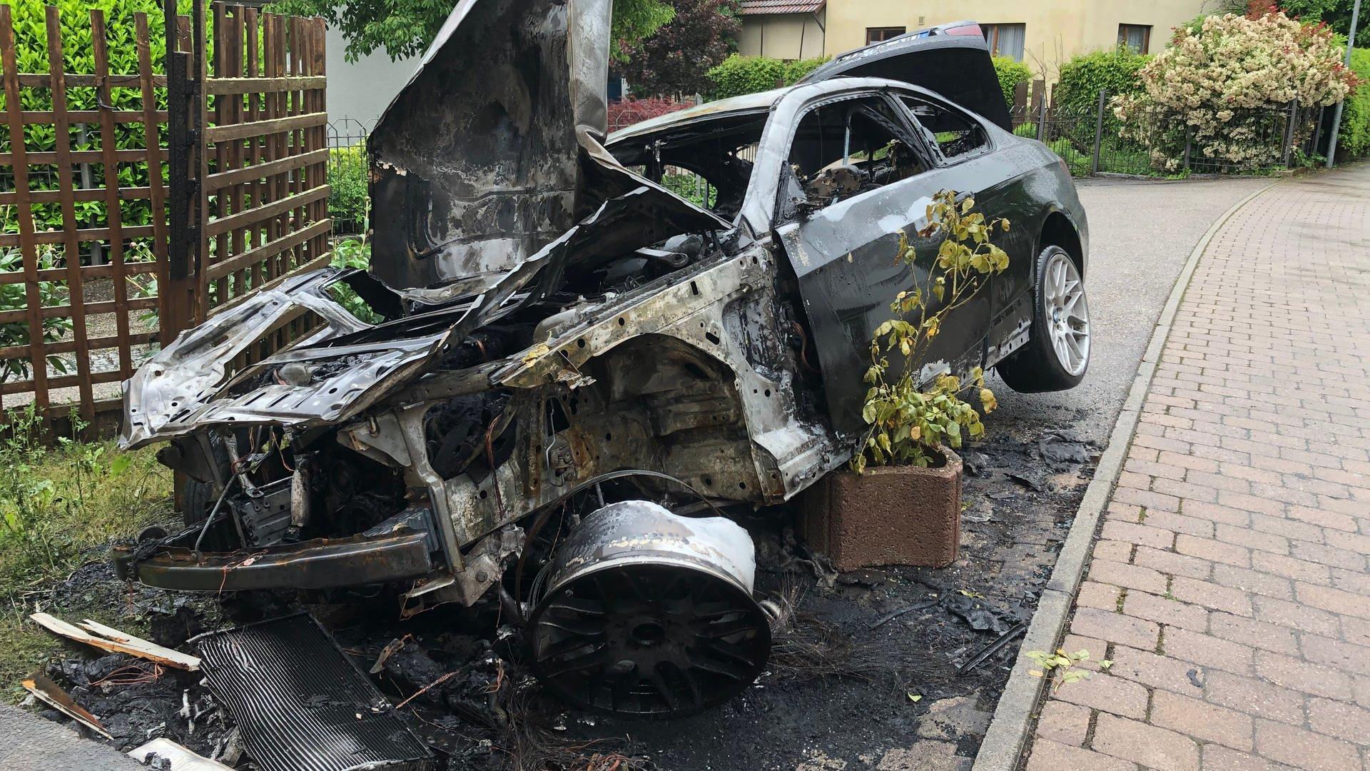 Ein Auto steht völlig ausgebrannt am Straßenrand: die Polizei vermutet nach einer Brandserie in Kirchardt Brandstiftung