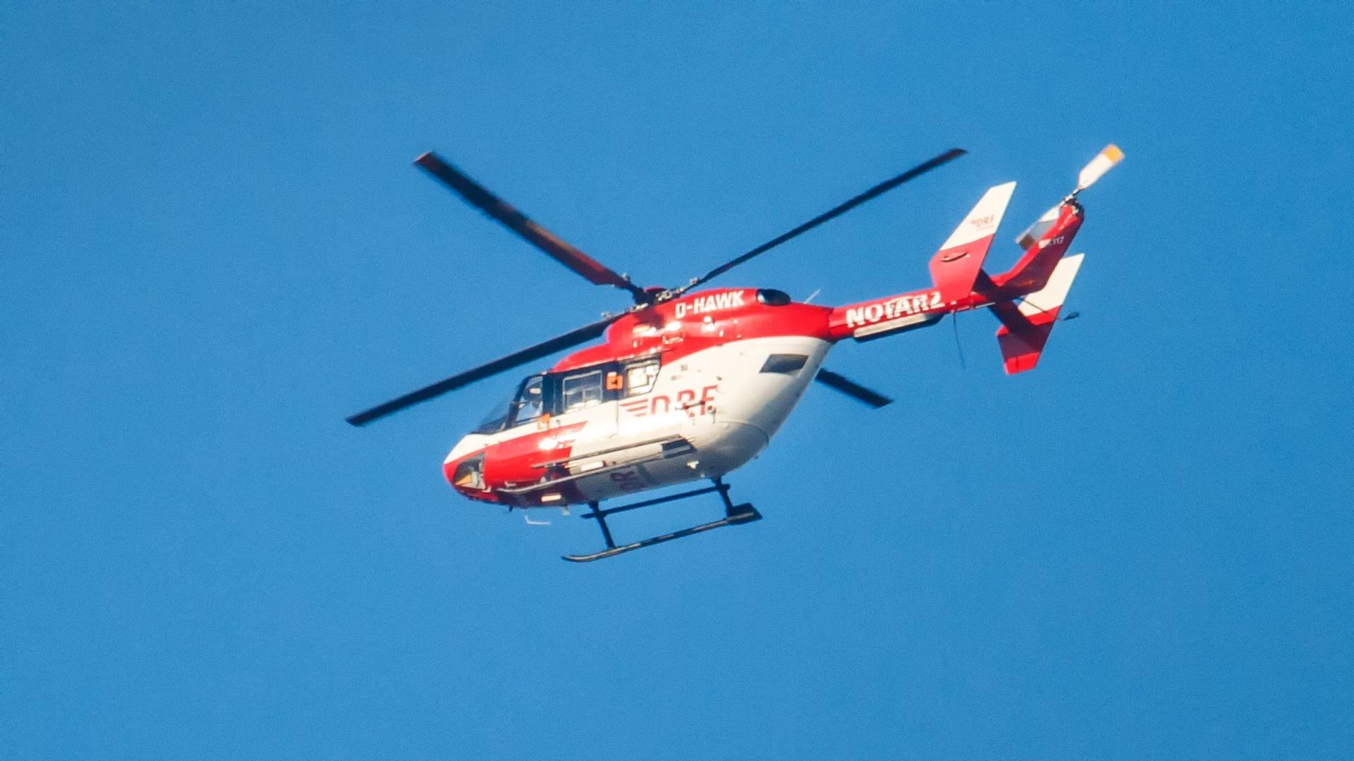 Ein roter Rettungshubschrauber am blauen Himmel