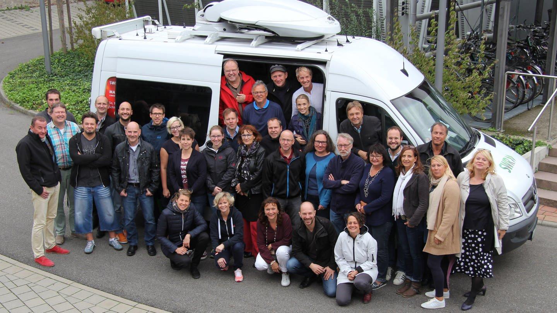 Das Team von Baden Aktuell im SWR Studio Karlsruhe steht rund um einen Übertragungswagen