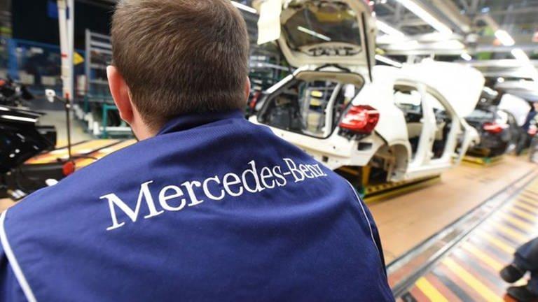 Mann mit Mercedes-Weste sitzt am Band, auf dem Autos produziert werden