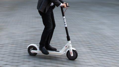 E-Scooter wird von Person in Stadtgebiet gefahren (Foto: dpa Bildfunk, Picture Alliance)
