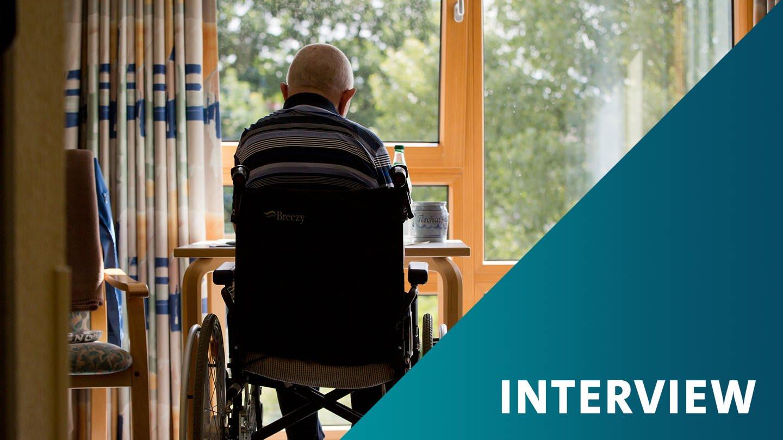 Ein Senior sitzt in einem Rollstuhl in einem Pflegeheim
