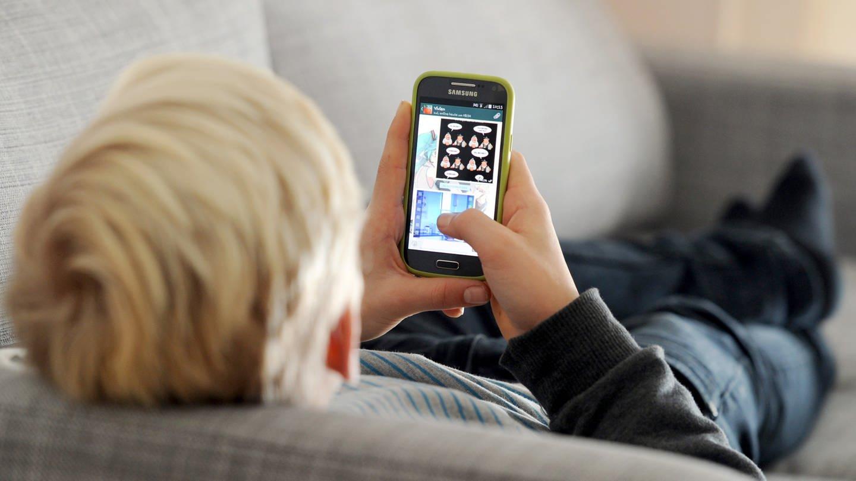 Jugendlicher liegt auf einem Sofa und blickt auf sein Smartphone. (Foto: dpa Bildfunk, Tobias Hase)