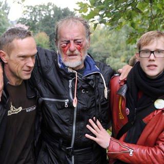 Zwei Männer stützen im Schlossgarten in Stuttgart den durch einen Wasserwerfer verletzten Dietrich Wagner. Tausende hatten gegen das Bahnprojekt Stuttgart 21 demonstriert und wollten am 30. September 2010 das Fällen von hunderte Jahren alten Bäumen verhindern. (Foto: dpa Bildfunk, picture alliance / dpa / Marijan Murat)