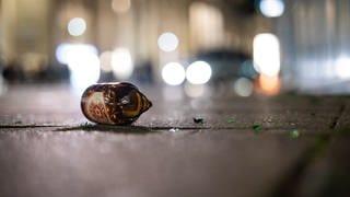Eine zerbrochene Bierflasche liegt auf dem Schlossplatz. In der Nacht gab es rund um den Schlossplatz Auseinandersetzungen zwischen Jugendlichen und der Polizei.  (Foto: dpa Bildfunk, picture alliance/dpa | Christoph Schmidt)