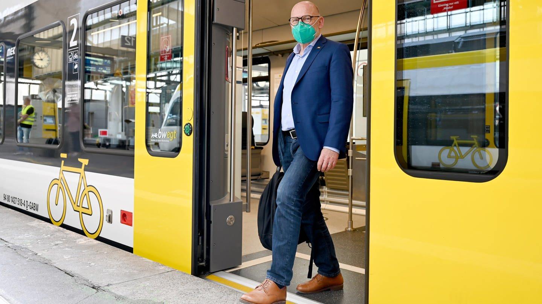 Winfried Hermann (Grüne), der Verkehrsminister von Baden-Württemberg, steht im Eingang eines Regionalzugs