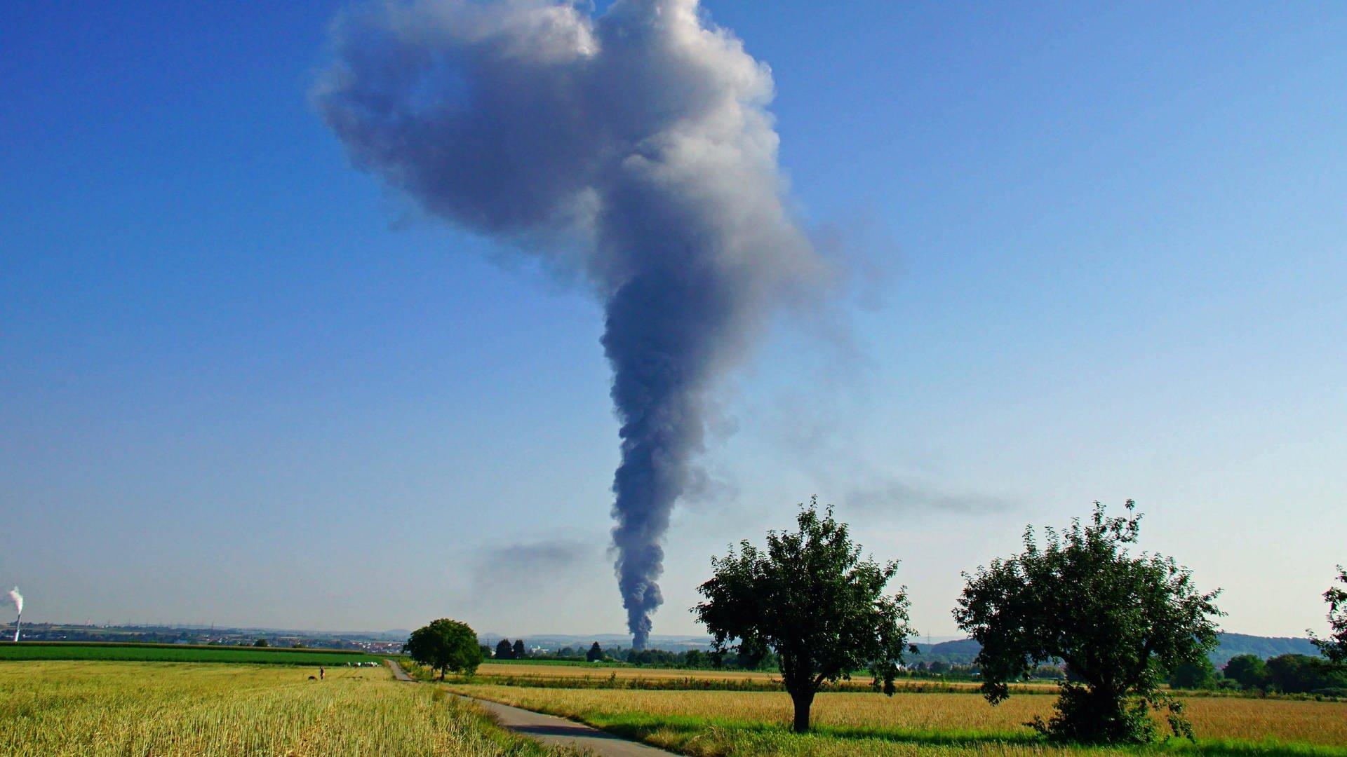Eine riesige schwarze Rauchwolke ist von einer Wiese aus zu sehen.