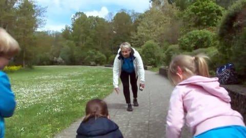 Eine Frau steht vor Kindern und machte eine Übung vor