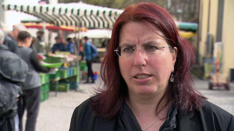 Frau steht auf einem Markt und spricht