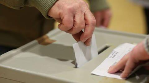 Wahlzettel beim Einwurf in die Box (Foto: dpa Bildfunk, picture alliance/dpa/Matthias Bein)