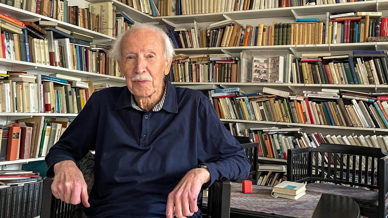 Professor Hermann Bausinger in seinem Wohnzimmer vor Wänden voller Bücher