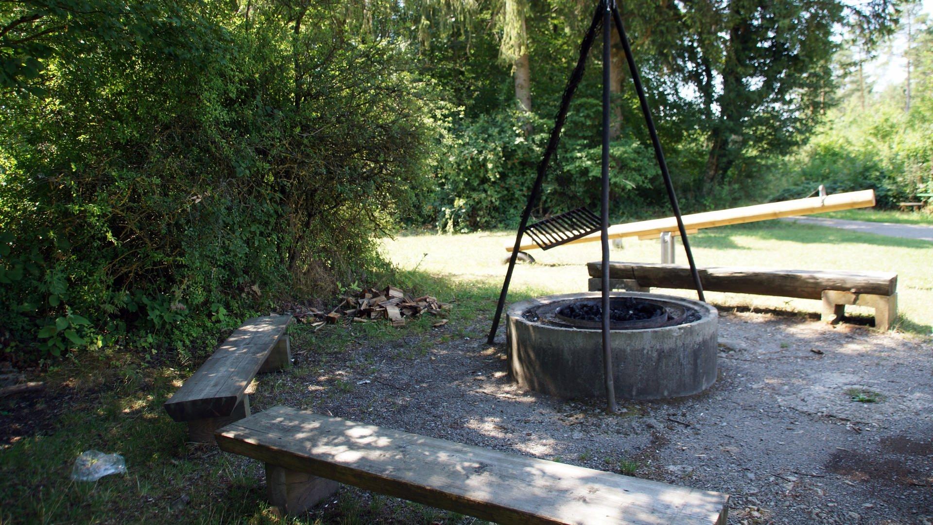 Eine Grillstelle im Wald mit hängendem Rost über betongefasster Feuerstelle.