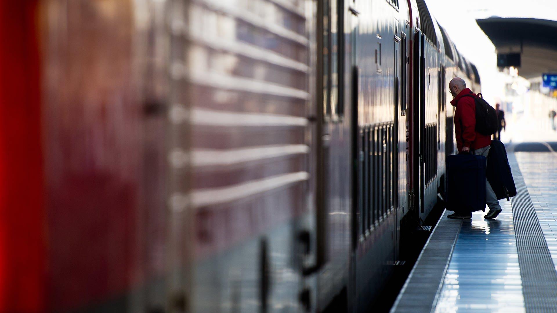 Mann steigt in Zug ein
