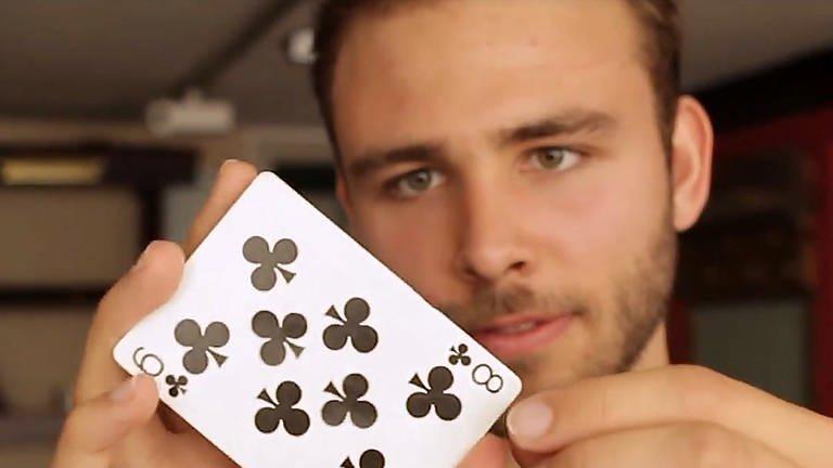 Der Zauberer Nikolai Striebel zeigt einen Kartentrick; Foto: SWR