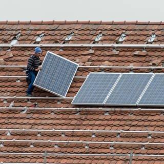 Mann bringt auf einem Dach Photovoltaikmodule an (Foto: dpa Bildfunk)