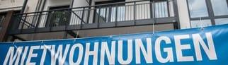 """Ein Banner mit der Aufschrift """"Mietwohnungen"""" hängt vor einem Gebäude mit mehreren Wohnungen. (Foto: dpa Bildfunk, picture alliance/Silas Stein/dpa)"""