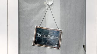 In einem geschlossenen Geschäft hängt ein Schild mit der Aufschrift «geschlossen». (Foto: dpa Bildfunk, picture alliance/dpa/dpa-Zentralbild | Britta Pedersen)
