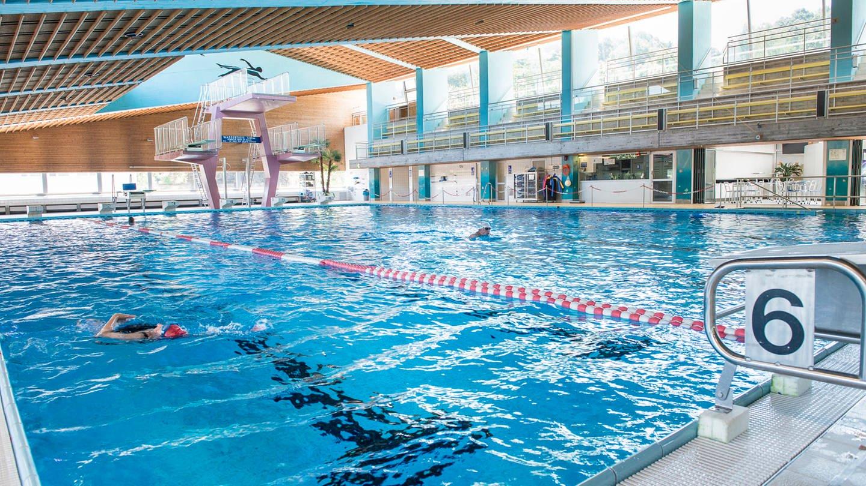 Ein Hallenbad von innen, Schwimmbecken und wenige Schwimmer