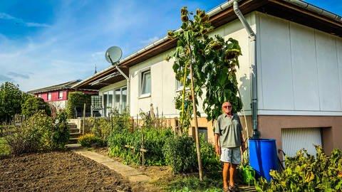 Ein Mann steht neben einer riesigen Sonnenblume in seinem Garten (Foto: SWR, Peter Köpple)
