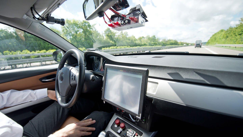 Ein Auto fährt auf einer Autobahn, ohne dass der Fahrer die Hände am Steuer hat (Foto: dpa Bildfunk, picture alliance/Daniel Naupold/dpa)
