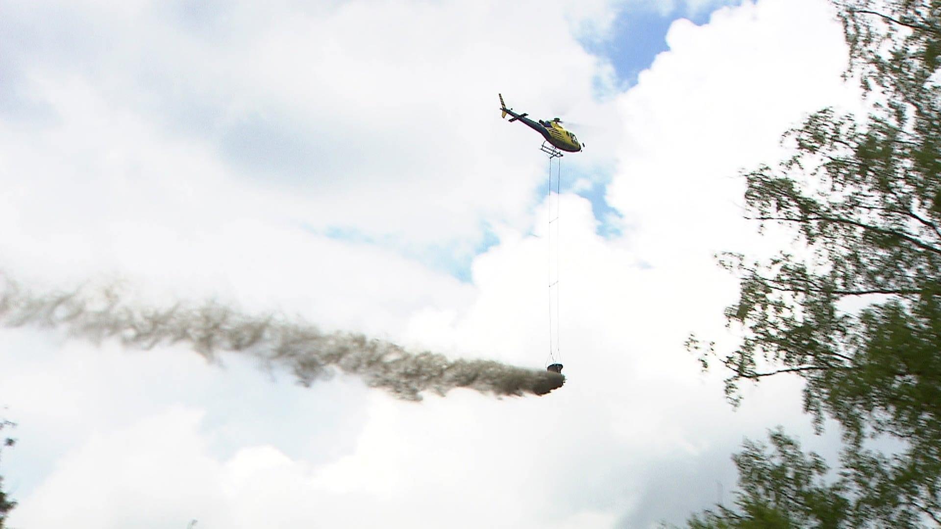 Hubschrauber fliegt über Waldgebiet und verteilt Kalk